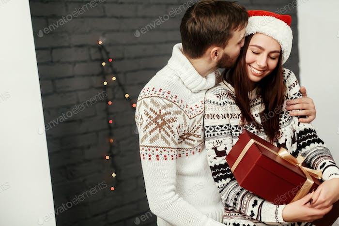 Handsome romantic man kissing & hugging emotional brunette woman