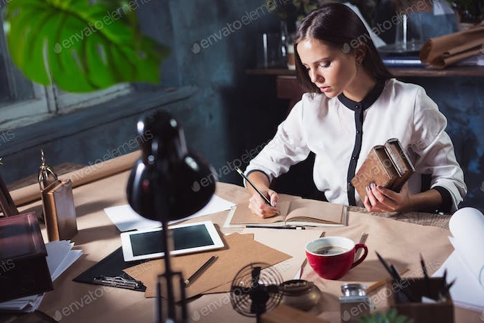 Young beautiful woman working with cup of coffee