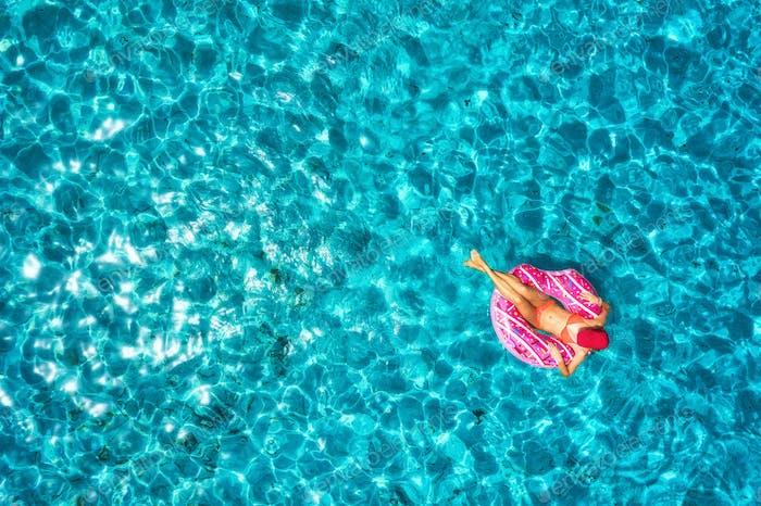 Luftaufnahme der Frau auf dem Schwimmring im Meer
