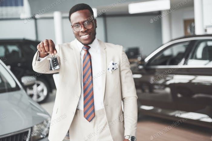 The young attractive black businessman buys a new car, he holds the keys in his hand