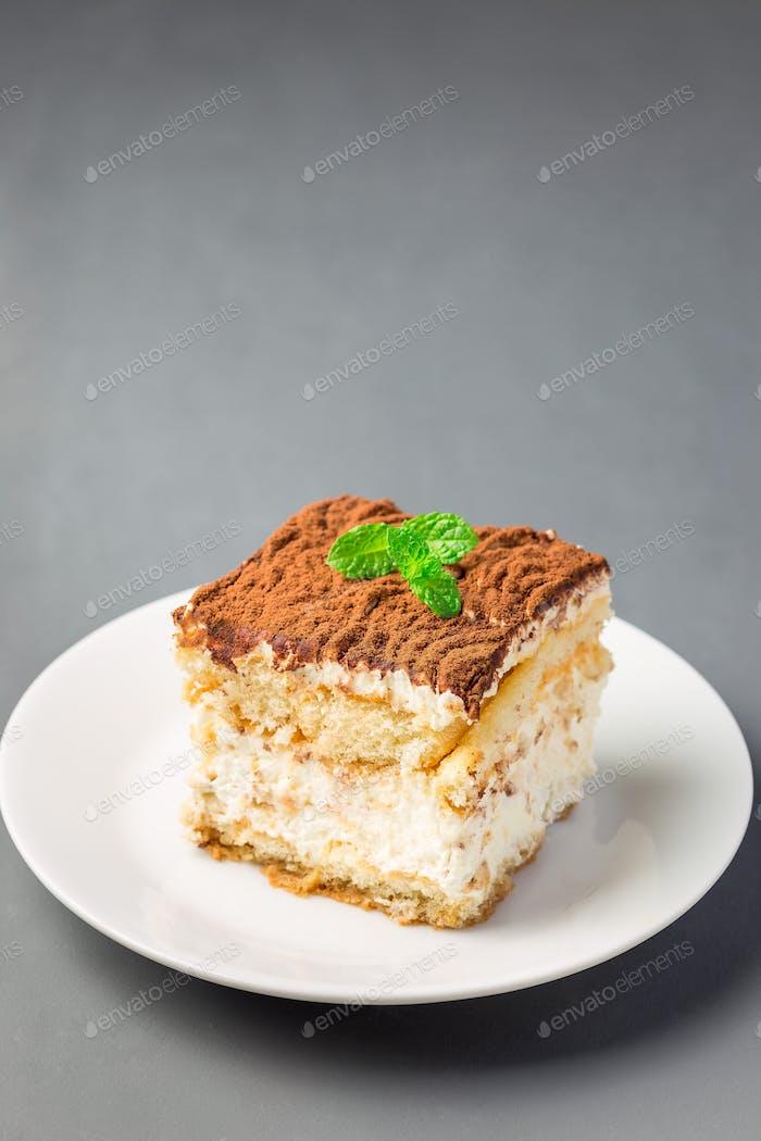 Stück traditioneller italienischer Tiramisu Dessertkuchen auf weißem Plat