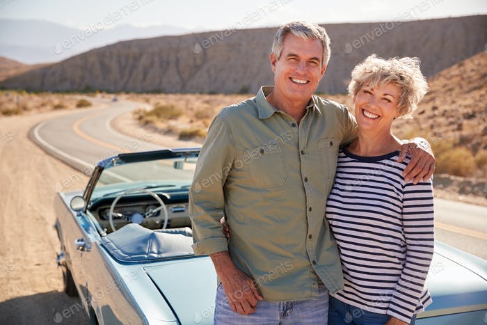 Senior couple on road trip standing by car smiling to camera