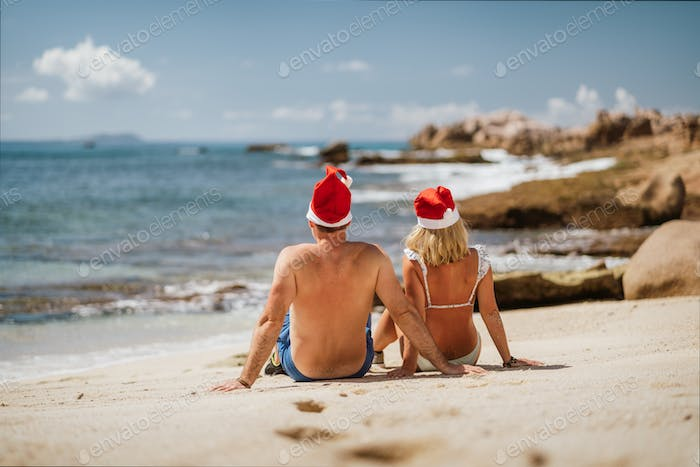 Tanned couple wear Santa Claus hat on tropical beach - Christmas or New Year's escape vacation
