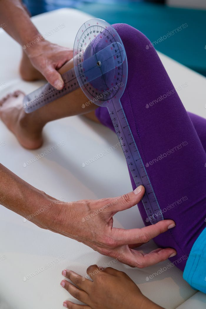 Physiotherapist examining girl patients leg with goniometer