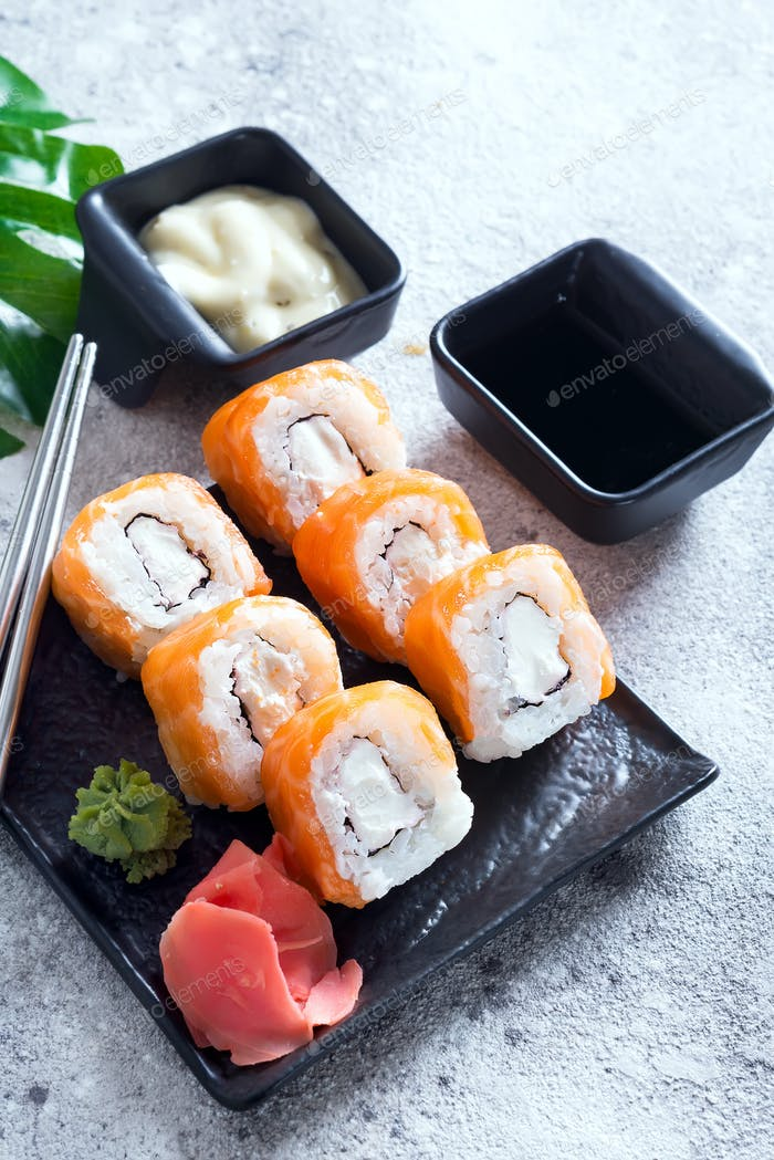 cream cheese Philadelphia roll classic on a stone black plate with chopsticks and sauce . Japanese