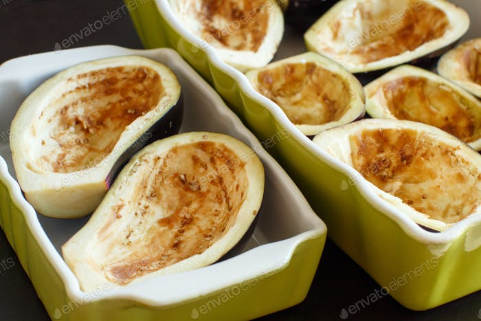 Halves of eggplants in baking pans close up