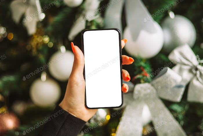 hand holding smart phone mobile near christmas tree