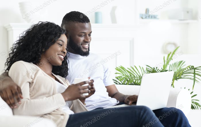 Cheerful black couple sitting on couch looking at laptop screen