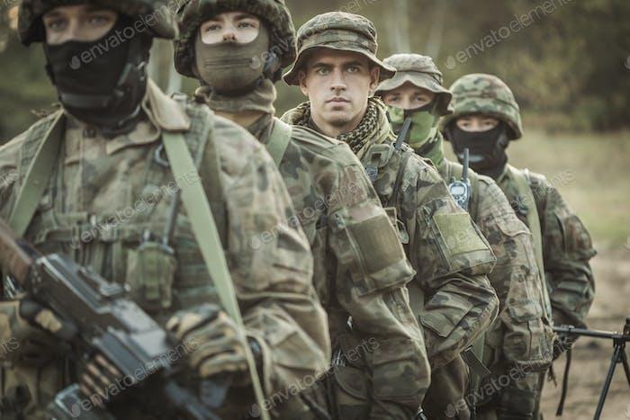 Bewaffnete junge maskierte Soldaten