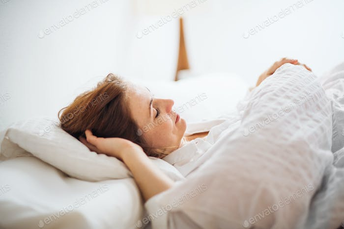 A young woman lying in bed indoors in the morning in a bedroom, sleeping.