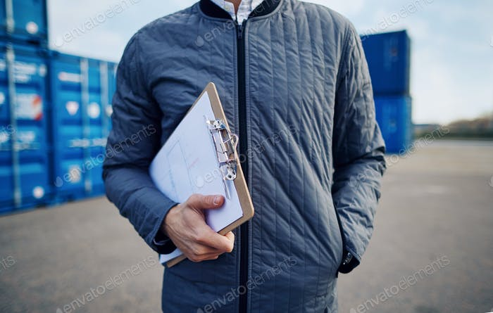 Foreman standing in a shipping yard holding an inventory clipboard