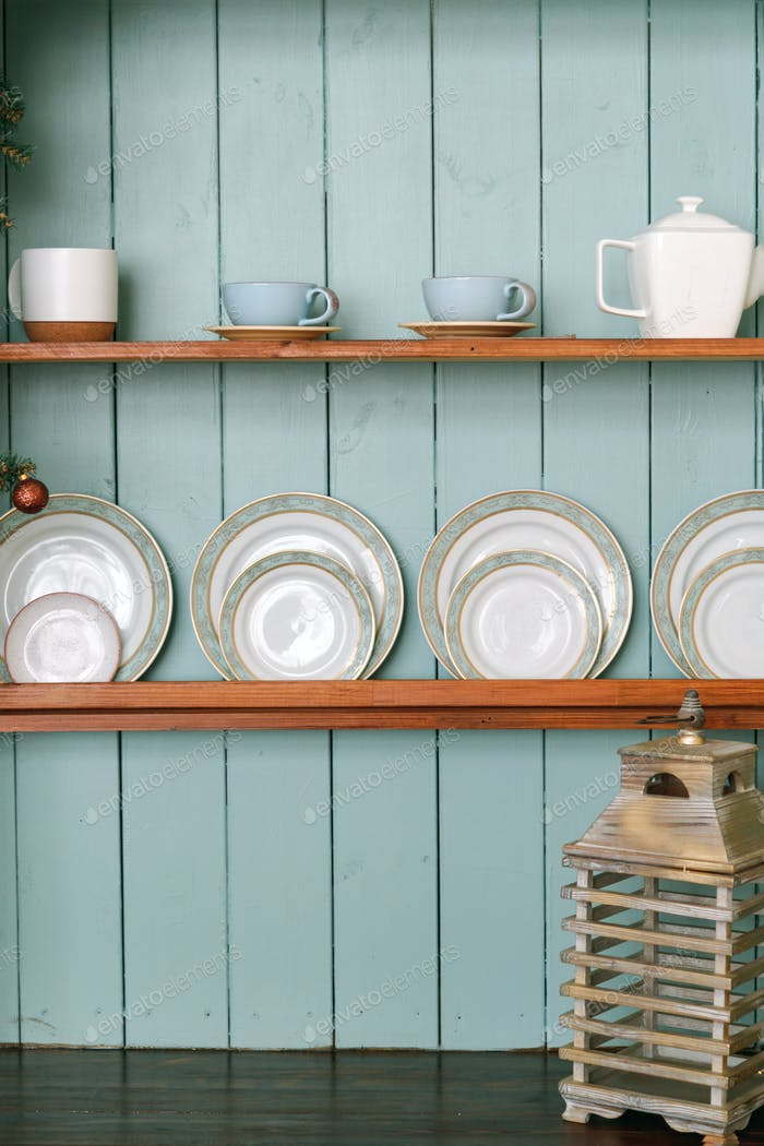 Rustic wooden shelves with ceramic utensils, plates and tea set