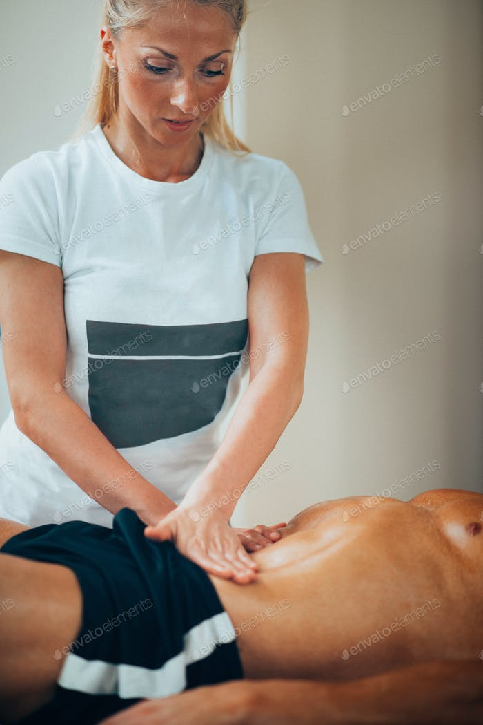 Stomach massage. Physical therapyst massaging sportsman's stomac