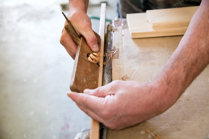 Carpenter using a planer on a plank of wood