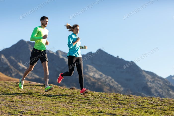 Healthy young couple running on mountain trail in the morning.