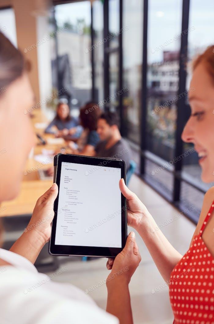 Nahaufnahme von zwei Geschäftsfrauen mit Blick auf das digitale Tablet im freigegebenen Büroarbeitsbereich