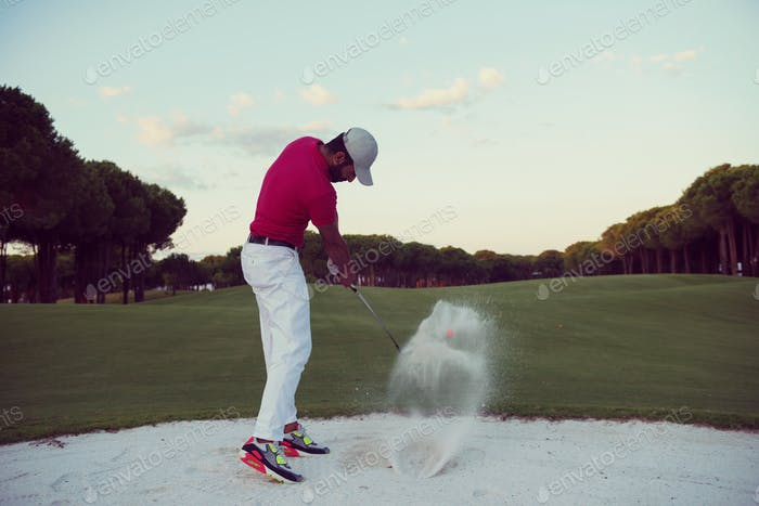 golfer hitting a sand bunker shot on sunset