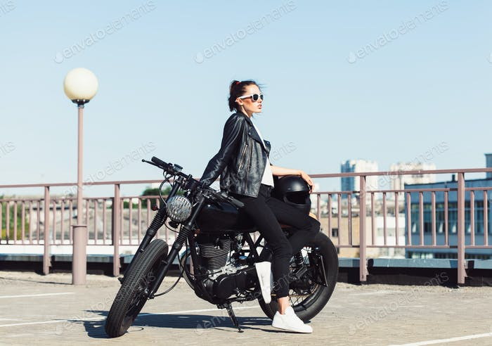 Biker girl sitting on vintage custom motorcycle
