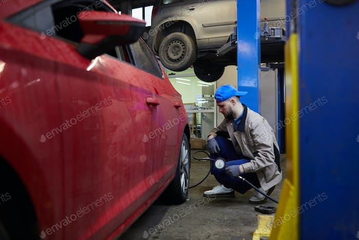 Repairman Using Tire Pressure Gage