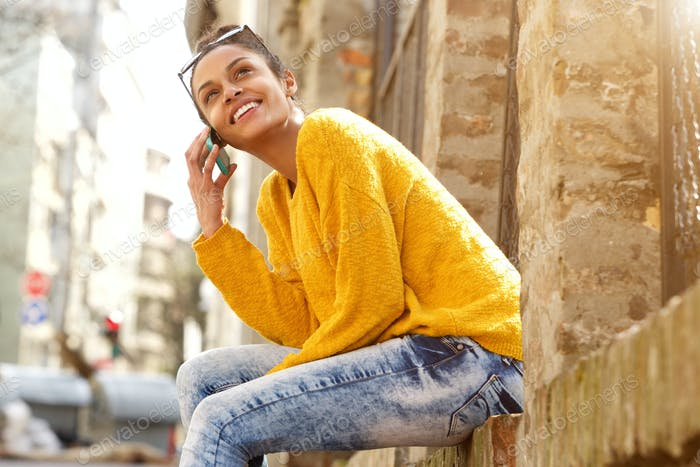 Attractive woman sitting outdoors and talking on cellphone