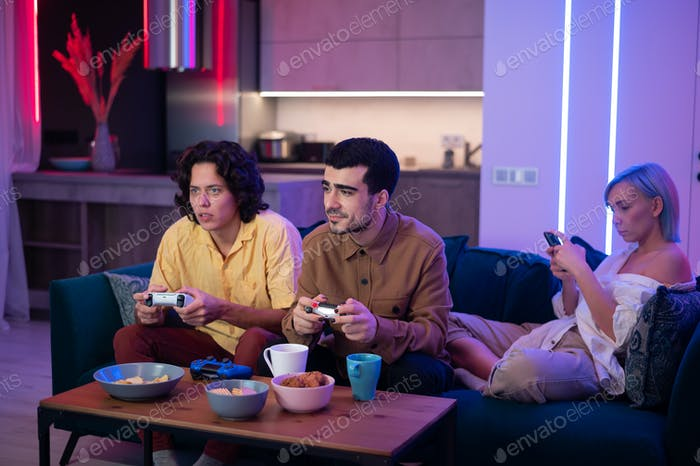 Gesellschaft der Freunde genießt es, sich auf der Couch zu entspannen, Videospiele zu spielen und Spaß in modernem Flach zu haben