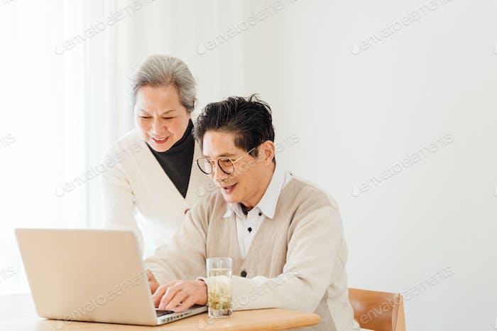 Senior-Paar mit Laptop zu Hause