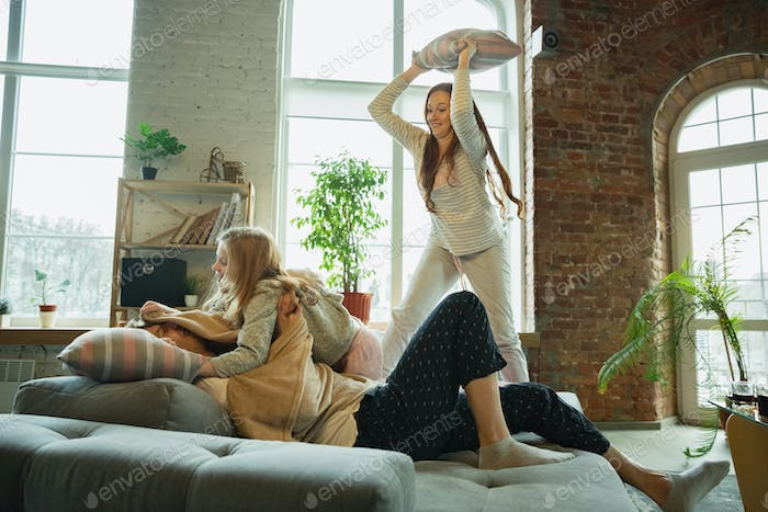 Family spending nice time together at home, looks happy and cheerful, fighting with pillows
