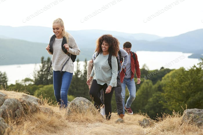 A group of mixed race young adult friends smiling while hiking to a mountain summit