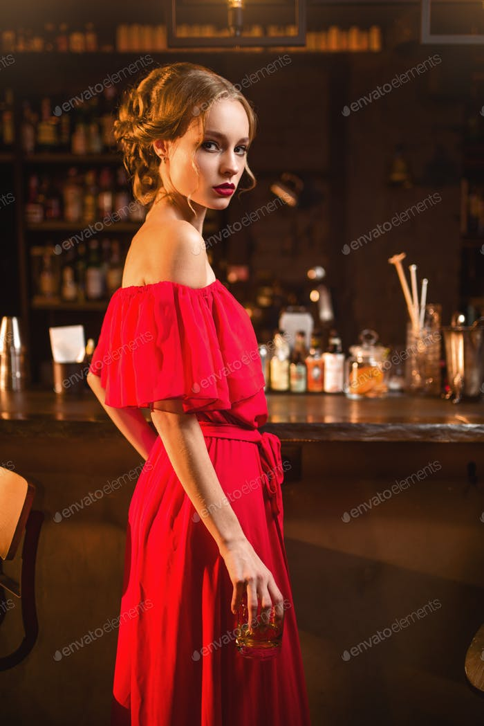 Woman in red dress standing at the bar counter