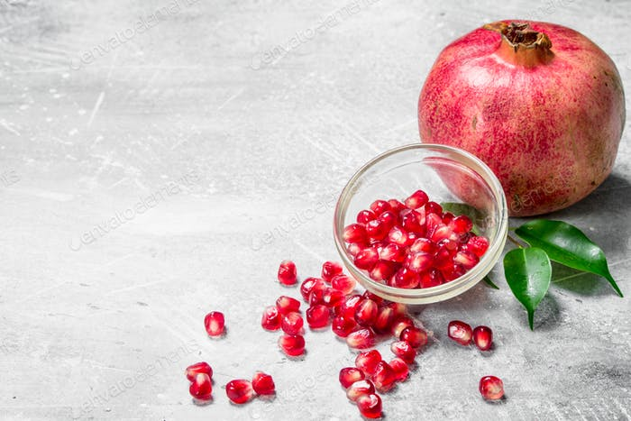 Pomegranate seeds and a pomegranate with leaves.