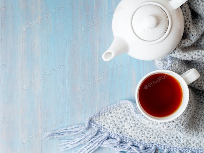 tea, teapot, copy space, warm knitted scarf on blue wooden background, cozy house, top view