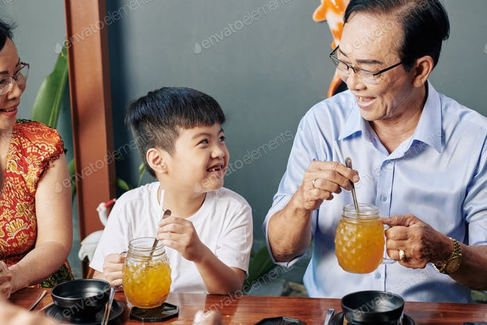Boy resting in cafe with grandparents
