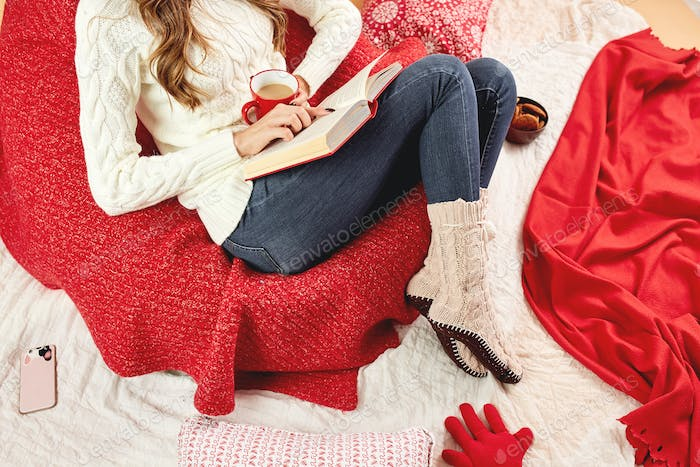 Girl dressed in white knitted sweater, jeans and knitted socks reads a book lying on red-white
