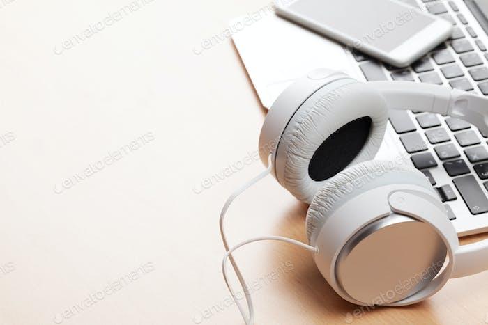 Kopfhörer über Laptop auf Holzschreibtisch