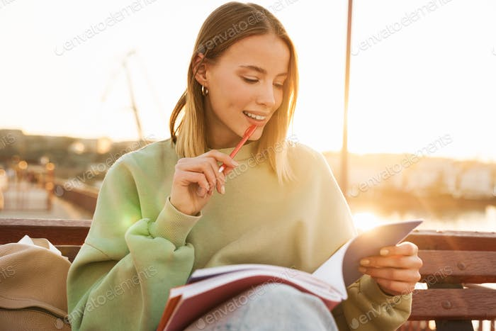Portrait of woman studying with exercise books while sitting on bench