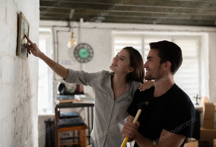Cheerful woman showing picture to boyfriend in new apartment