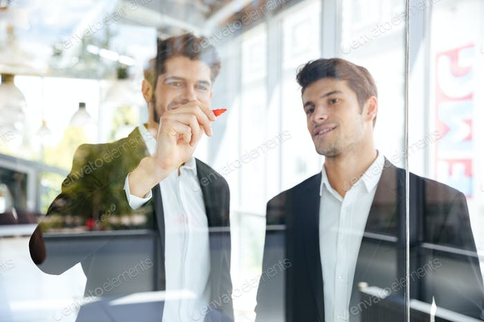 Two happy businessmen writing on glass board in office