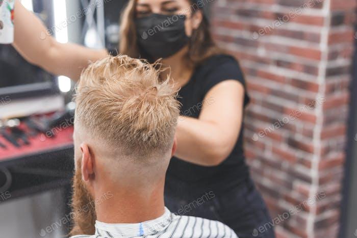 Hair styling in women barbershop. Spray