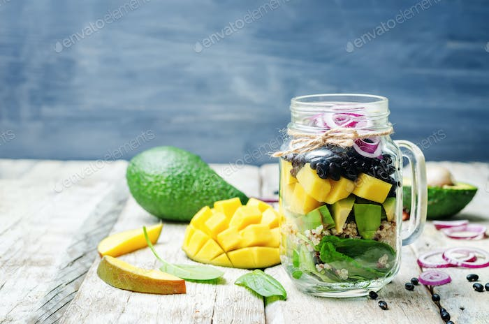 homemade healthy salads with black beans, vegetables, fruits, an