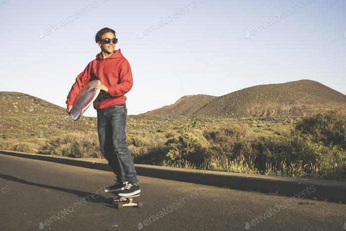 young beautiful male teenager go on skateboard holding surf board