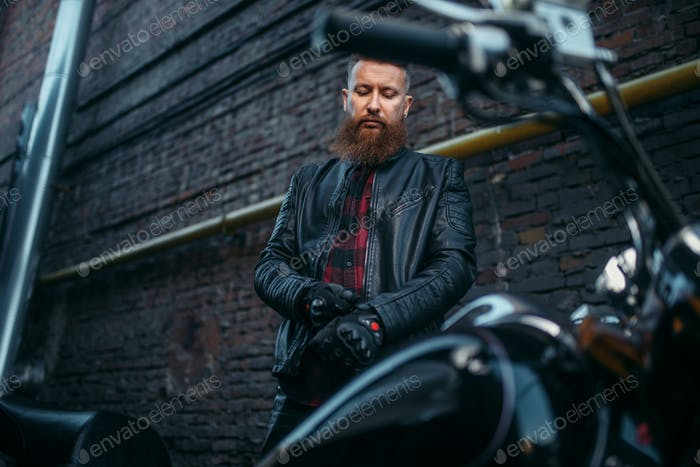 Male biker in leather jacket puts on gloves