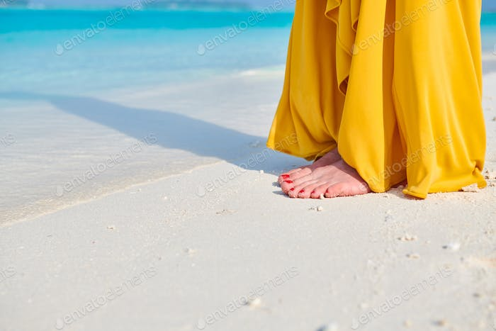 Woman legs in yellow dress on tropical beach