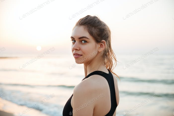 Young runner woman smiling happy resting after jogging training