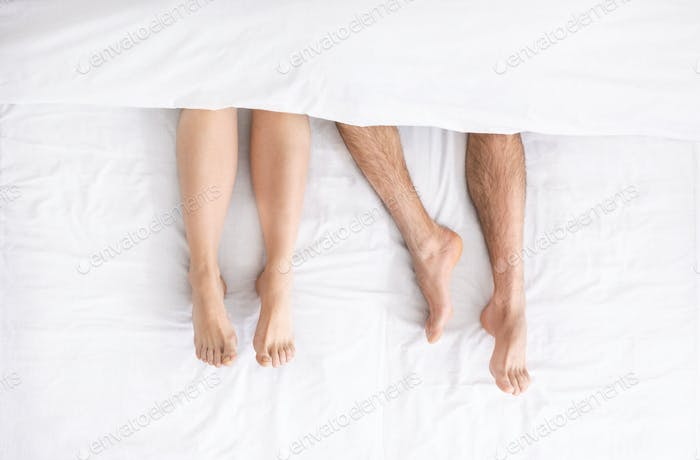 Millennial couple legs under duvet laying on bed
