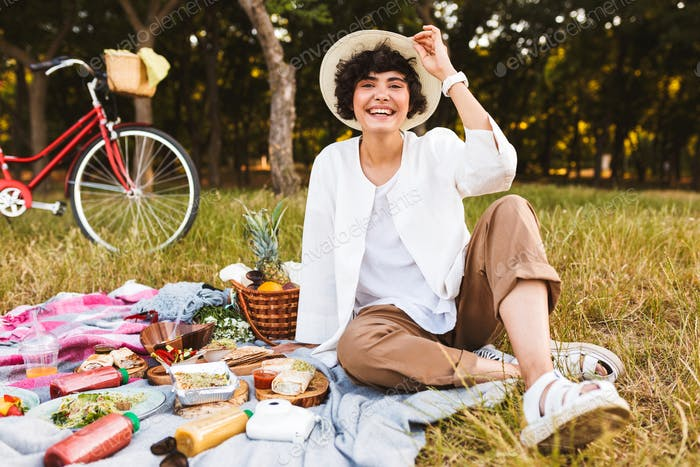 Pretty laughing girl sitting in hat and white shirt happily look