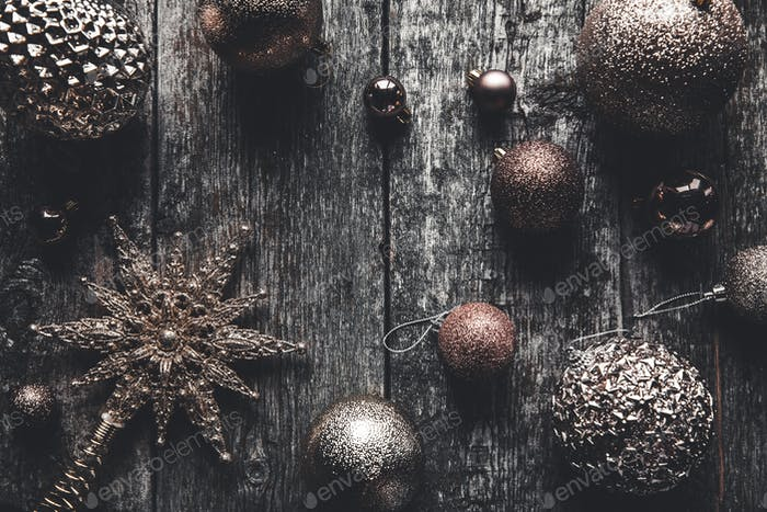 Christmas or New Year rustic wooden background with toy decorations, top view, copy space