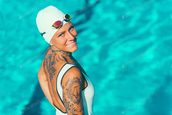 Portrait of female swimmer with tattoos posing by the pool