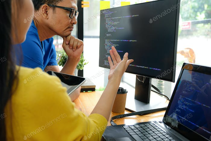 Asian female programmers are pointing at their laptop screen for presentation to executive.