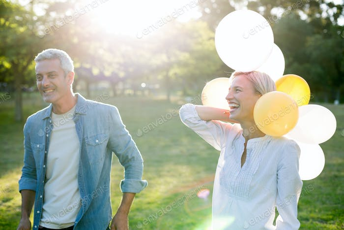 Happy couple with balloons at the park on a sunny day