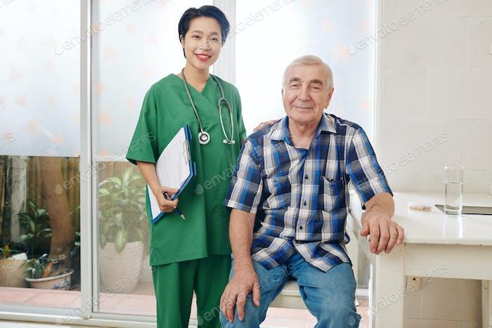 Positiver Senior Mann und seine medizinische Krankenschwester